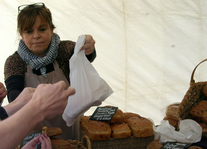 A trader sells fresh bread to a customer