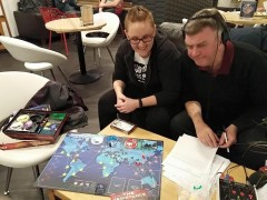 Organiser Millie teaching BBC Radio Lancashire's Gilly the Pandemic Board Game