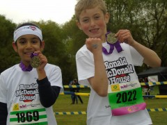 Tia Patel and James Wilkinson with their medals after completing a Mini Marathon