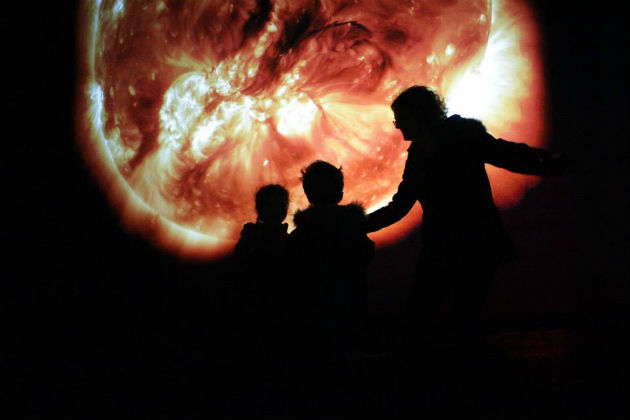 Visitors pose infront of the Sun at Night exhibition
