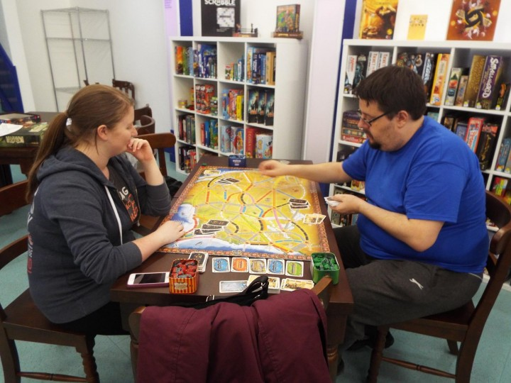 Emmi Bowles being shown the rules of Ticket to Ride.
