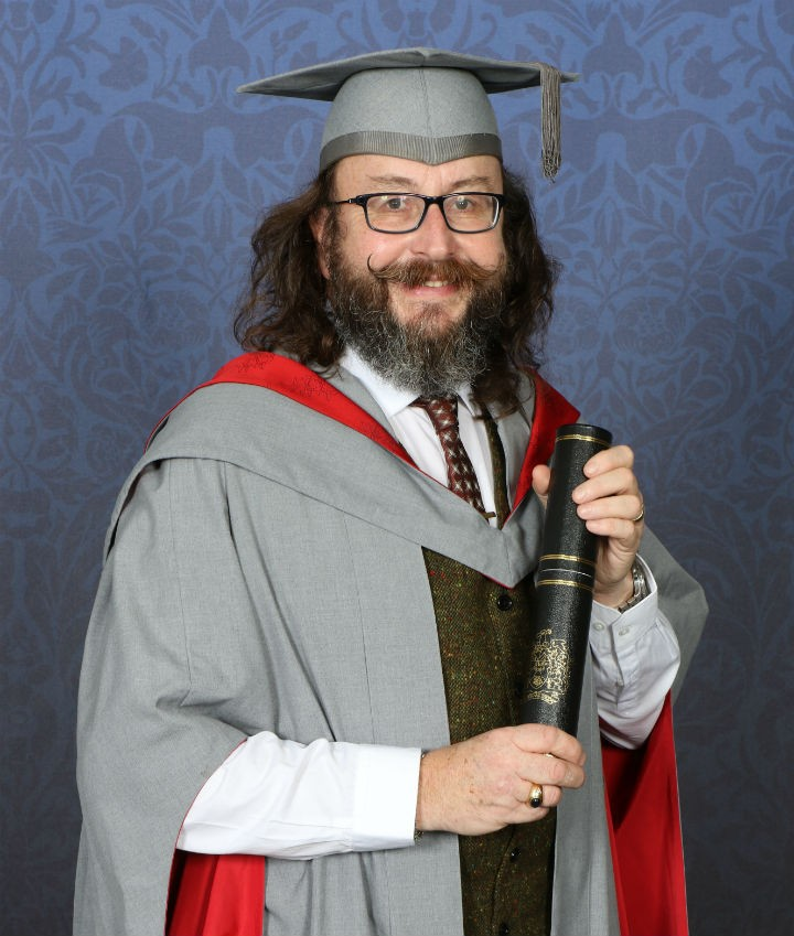 One half The Hairy Bikers with his scroll and gown