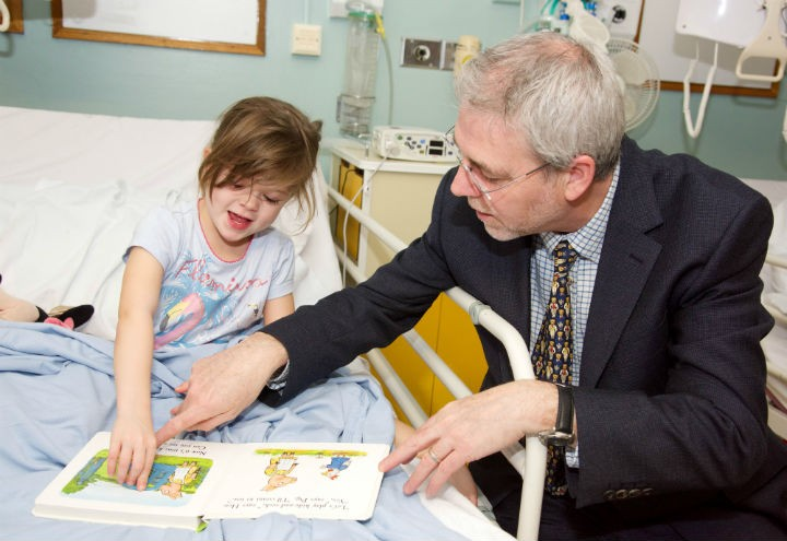 Three-year-old Evie enjoying Hide-and-Seek Pig, her new lift-the-flap book, with UCLan vice-chancellor Professor Mike Thomas