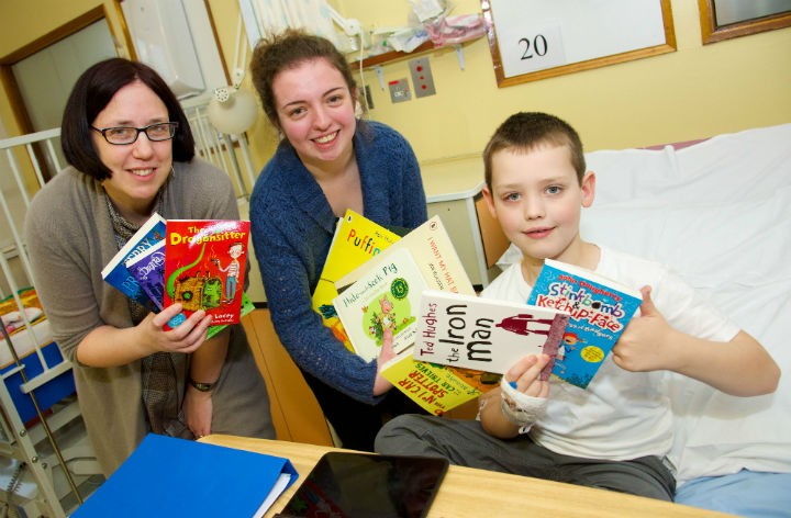 Avid reader Freddie, eight, gives the selection of books his thumbs up with UCLan's Dr Helen Day and student Jessica Sneddon