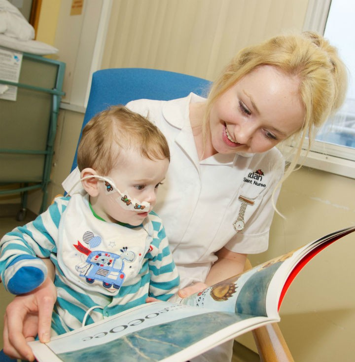 Nine-month-old Sam liking the colourful pictures in his new Red Sledge book with second year UCLan children's nursing student Kimberley Culshaw
